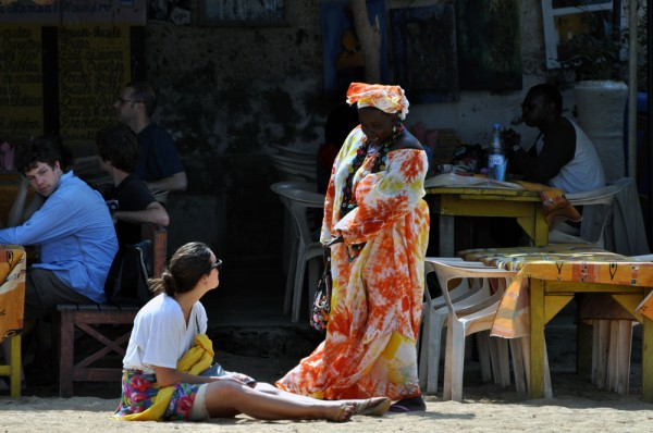 A colorfully dressed woman talks to a tourist on Goree Island in Senegal