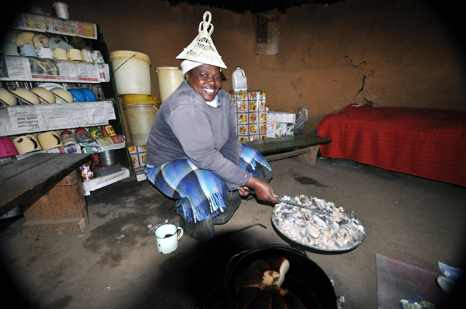 Basotho woman in Lesotho cooking bread over the fire