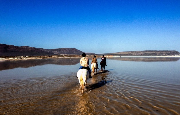 Riding across the shallow waters of Nordhoek beach