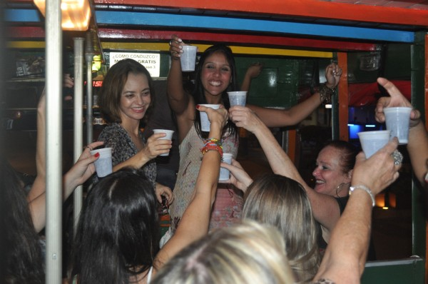 Girls toast their drinks as the Chiva rolls through town