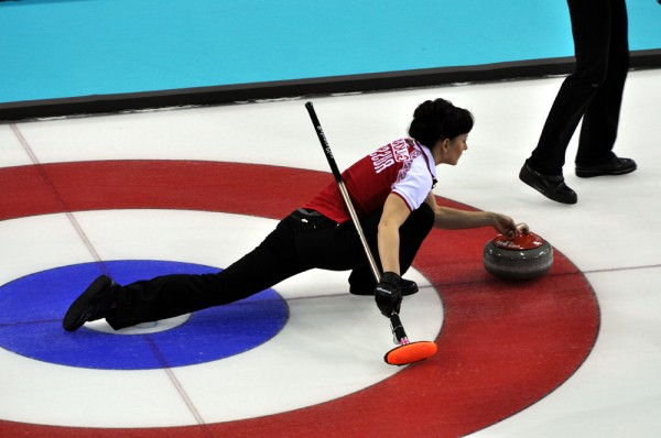 Russia's Ekaterina Galkina prepares to deliver a curling stone against the USA