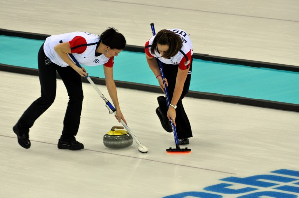 Sweeping the ice in front of the moving curling stone allows control of speed and direction