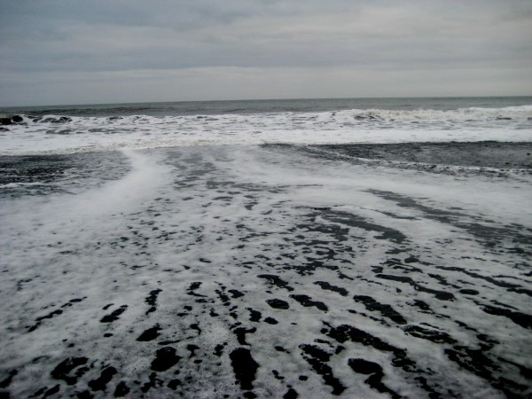 The ocean crashes over the black sand beach of Vik.