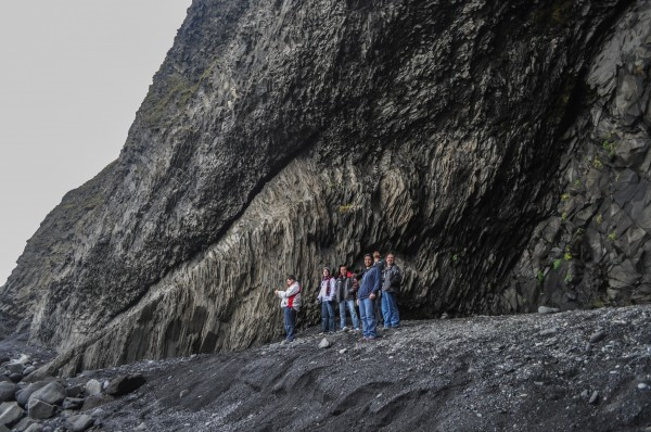 My friends and I perched on the edge of the giant basalt cave at Reynisfjara with the ocean crashing nearby.