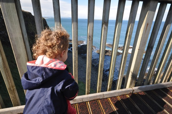 Our daughter looking out at the crashing waves below Dunluce Castle.